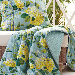 Hydrangea Qulit - As bright and cheery as a summer day, this quilt is a lovely layer tossed at the foot of a bed or on a porch swing. Hued in sunny shades of yellow, leaf green and sky blue, the hydrangea floral has the dappled look of a hand-painted watercolor. Quilted with lattice stitching, it reverses to a classic blue ticking stripe for a whimsical play of pattern. Complete the charming look with the Hydrangea Euro Sham (sold separately). 100% cotton.