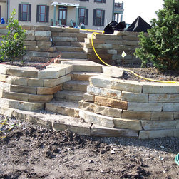 Retaining Wall - A natual stone retaining wall made of Buckskin Irregular Wallstone.  Installation by Springwater Greenhouse & Landscaping, stone supplied by Sturgis Materials.