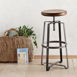Industrial Stool - A fusion of raw steel and solid wood, this versatile seat swivels up and down to easily adjust from counter to bar to drafting table.