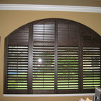 Regency - Here is an example of an arched window with a custom stain wood plantation shutter. 4panel with the top area closing independent of the bottom