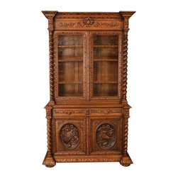 Pre-owned Antique 1880 Oak French Provincial Hunting Buffet - This handsome antique French buffet dates to 1880 and boasts great oak carvings in the traditional Hunting style! The original glass on the upper two doors has been replaced with chicken wire, making it a perfect choice for your French Provincial or rustic dining room or kitchen. Barley twist carvings frame the oak buffet or sideboard, and foxy looking creatures peer out from the two drawers. This fine French antique stands nearly 9 feet high at 103 inches, and measures 56.75 inches wide by 22 inches deep.    Overall Condition is Used - Good. Shows normal wear to the finish and miscellaneous nicks, dings, and scratches due to age and use. The original glass in the upper doors was broken and has been replaced with chicken wire.