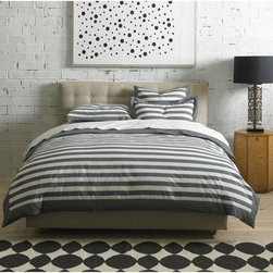 DwellStudios Duvet Set - Graphic Stripe Ink - Bold, clean and modern, DwellStudio's sublimely simple Graphic Stripe duvet set adds effortless style to the bedroom. Their designers put their unique spin on this bedding by coloring the stripes with a chic gray hue. Their team also added a bold border trim that lines the duvet cover and shams. Each set is constructed at the best Oeke-Tex certified mills in Portugal, and they only use environmentally friendly Oeke-Tex certified dyes. The patterns are printed onto luxurious 300-thread count woven cotton sateen that is combed three times on each side, which gives the fabric its silky soft feel. Their duvet covers feature a unique hidden button closure for effortless insert assembly, and each set includes two French-back shams, a DwellStudio signature detail. The Graphic Stripe Ink Duvet Set pairs beautifully with our Pintuck Pearl Sheet Set.