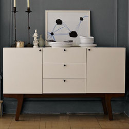 New Dumont Buffet - Northern light, heavy on the storage space. Mid-century Scandinavian design inspired this highly detailed white-lacquered dining room buffet, which houses three deep drawers and two roomy cabinets, each fitted with an adjustable interior shelf to accommodate anything from short stacks of plates to tall pitchers. The streamlined, storage-rich piece is lofted on angled solid wood legs in a light pecan stain.