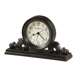 Howard Miller - Bishop Tabletop Clock w Wood Mantel Base and - Intricately carved clock is a beauty on your table top or on a mantel. Its base is narrow enough to fit above the fireplace. Made of hardwoods and veneers and finished in an aged black with red undertones. The round dial is classic and is nestled in the carved base. This decorative metal and wood alarm clock features an aged, off-white dial and has aged black Arabic numerals and black hands beneath a convex glass crystal. Felt bottom protects your desktop or table. Has red undertones. Quartz, alarm movement includes the battery. Worn Black Finish. Made of Hardwoods and Veneers. 9 in. W x 2 1/2 in D x 6 in. H