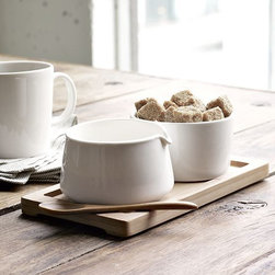 New Sugar + Creamer Set on Bamboo Tray - Set in ceramic. This elegantly simple creamer and sugar set in glazed white porcelain comes with a spoon and a lightweight bamboo tray that makes it easy to carry from counter to table or kitchen to dining room.
