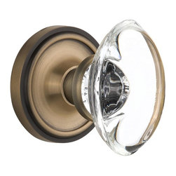 Nostalgic - Nostalgic Passage-Classic Rose-Oval Clear Crystal Knob-Antique Brass (NW-711320) - The simple elegance of the Classic Rosette in antique brass offers beauty and durability that will compliment a variety of architectural styles. Add our Oval Clear Crystal Knob, with its clean oval shape and smooth outward-curve, and you have the perfect accompaniment for Period, Rustic and Arts & Crafts style homes. All Nostalgic Warehouse knobs are mounted on a solid (not plated) forged brass base for durability and beauty.
