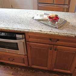Kitchen Remodel, Shaker Heights, OH #2 - This kitchen renovation consisted of installing Medallion Silverline Maple Door Style: Winston in White Chocolate Finish on the perimeters and Silverline, Maple Door Style: Winston in the Chestnut Finish for the island accented with Top Knobs Normandy Knobs and Pulls in Patina Rouge.  Artisan Granite Collection in Natural Stone Giallo Ornamental, with an Ogee Edge was used for the countertop and 4x4 Light Travertine, Tumbled tile for the backsplash.  The color palette and finishes for the kitchen were selected to bring in character, elegance and charm that compliments the rest of the Shaker Heights home.   Creamy painted maple cabinets with a contrasting island strike a balance between the refinished floor and new tile backsplash.  A custom pot rack was designed using cabinetry molding pieces allowing the cookware to be accessible but to also make a statement in the room.  The light creamy finishes are punctuated with darker accents that get noticed, like the bridge faucet, the medallion above the range and the cabinet hardware.