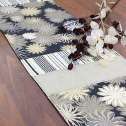Chooty & Co. - Chooty and Co Petal Faster Granny Black Reversible Pieced Table Runner - RPL7202 - Shop for Runners from Hayneedle.com! Make a chic statement of style with the Chooty and Co Petal Faster Granny Black Reversible Pieced Table Runner. This handily reversible table runner is crafted of a cotton/poly/rayon blend designed for color-fast durability. With a solid gray background this handsome table runner features subtle gray stripes and a bold contemporary floral pattern in black and shades of gold. Made in the USA. Hand-wash or spot-clean.About Chooty & Co.A lifelong dream of running a textile manufacturing business came to life in 2009 for Connie Garrett of Chooty & Co. This achievement was kicked off in September of '09 with the purchase of Blanket Barons well known for their imported soft as mink baby blankets and equally alluring adult coverlets. Chooty's busy manufacturing facility located in Council Bluffs Iowa utilizes a talented team to offer the blankets in many new fashion-forward patterns and solids. They've also added hundreds of Made in the USA textile products including accent pillows table linens shower curtains duvet sets window curtains and pet beds. Chooty & Co. operates on one simple principle: What is best for our customer is also best for our company.