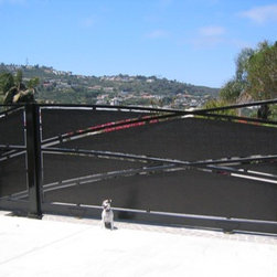 Custom Slide Gate with Pedestrian Gate - This modern gate has textured stainless steel panels inlay-ed on a tubular frame that has been rolled to give a dramatic entry. The pedestrian gate has been build to complement the entry gate and look as one..