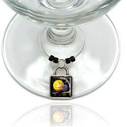 """Made on Terra - Planets Space Available Square Sun Moon Stars Wine Glass Silver Charm - Your guests have arrived and the atmosphere is electric. A sip of wine here, a sip of a cocktail there and you find the conversation turning to the charming baubles you've placed on the glasses, something special you chose for each of your eclectic guests. They love them and appreciate your thoughtfulness. You love them for their uniqueness and that no one forgets which glass they were using.  Choose from Made on Terra's many designs for the best party ever. Ring is 1"""" diameter; measures 2"""" from top of ring to bottom of charm. Made of metal and plastic. Sold individually."""
