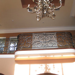 Wrought Iron Balcony Handrail - This stair system was hand forged out of raw steel. It was polished with a steel brush and then clear coated to preserve the natural beauty of the metal.