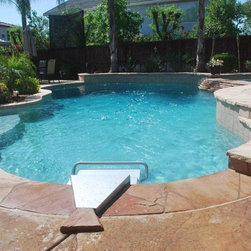 Endless Pools - Fastlane by Endless Pools - It's not the eccentric shape, stone steps, or nearby gazebo that let this pool function as a swimmer's paradise. It's the silver, railed unit front and center. That's the Fastlane swimming machine, by Endless Pools.