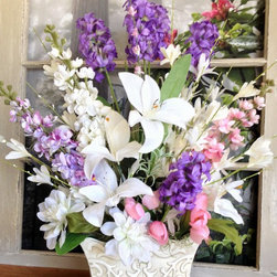 Floral Table Centerpieces - This is an elegant Spring floral table decoration arrangement that is professionally handcrafted with artificial Purple Hyacinths; Pink, White & Purple Delphiniums; White Lilies; Pink Tulips; White Dahlia's; and accent flowers. The container is an antiqued embossed metal container in an off-white color. Makes a wonderful Mothers Day Gift!!