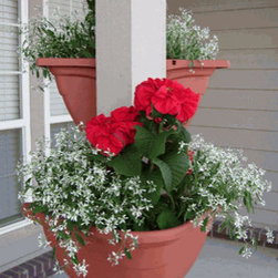 Plant Around Corner Planter - These planters are a clever way to take advantage of available space with gorgeous flowers. I love the idea of stacking them up a post for maximum effect.