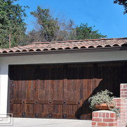Spanish Colonial Garage Door Project in Burbank, CA by Dynamic Garage Door! - Spanish Garage Doors are defined by their timeless rustic appearance such as this custom Spanish Garage door designed, crafted and installed by Dynamic Garage Door. It was handcrafted using select tight knot cedar and hand wire brushed to accentuate the rustic grain structure of the cedar wood. The garage door was actually stained in an oil-rubbed stain finish which is easily maintained over the years and give the wood that rustic Spanish style sought after in Spanish Colonial Architectural doors.