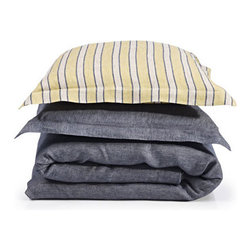 Riggs Striped Linen Bedding | Gracious Style - Riggs is denim-blue bed linen combined with a bold yellow stripe. This young, sleek style is ideal in a modern bedroom. The pre-washed look in combination with the strong Navy Blue make this bedding unique. Sheets and duvet covers are available in Navy Blue. Pillow cases and shams, finished with a flounce, are available in Navy or Straw Stripe.