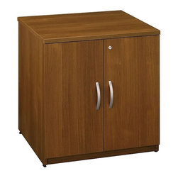 Bush Business - Locking Storage Cabinet in Warm Oak - Series - Levelers adjust for stability on uneven floors. Matches height of Desks, Credenzas and Lateral File for side-by-side configuration. One adjustable shelf provides storage versatility. PVC edge banding around top surface resists bumps and collisions. Accepts Storage Hutch 30 in. for additional storage capability. Rear wire access makes cabinet great for printer or peripheral storage. Durable melamine top surface is scratch and stain resistant. European-style, self-closing, adjustable hinges. Locks for privacy. 29.449 in. W x 23.346 in. D x 29.724 in. H (97 lbs.)