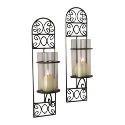 Danya B. - Set of Two Metal Filigree Wall Sconces - Madeira - Add contemporary elegance to your wall with this set of two rustic black iron wall sconces. The smoky glass inserts are hurricane shaped, so you get to have your pick of candles to place within them and feature on your wall in refined splendor.