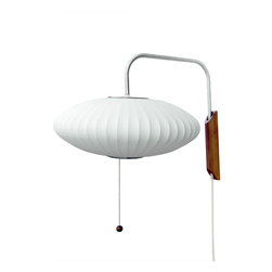 Modernica - Bubble Lamp, Saucer Sconce - Designer George Nelson helped define midcentury style, and this adjustable wall sconce epitomizes his visionary aesthetic. The solid-walnut wall mount supports a translucent plastic ellipse that swivels left to right and up and down for ultimate flexibility. Easy plug-in installation and soft, diffused light demonstrate why this classic is still in demand.