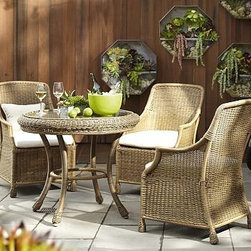 """Saybrook All-Weather Wicker Round Bistro Table & Armchair Set - Create a welcoming setting for outdoor meals with our Saybrook dining set, patterned after the wicker porch furniture once found throughout the American South. The bistro table is inset with a glass top, and the high-backed dining chairs have scooped arms for extra comfort. Click to read an article on {{link path='pages/popups/saybrook-care_popup.html' class='popup' width='640' height='700'}}recommended care{{/link}}. Table: 36"""" diameter, 30.5"""" high Chair: 23"""" wide x 27"""" deep x 37"""" high Frame crafted of welded aluminum and handwoven resin. Crafted from a durable synthetic that replicates the look and feel of wicker, but is impervious to sun, rain, heat and cold. Table features a tempered-glass top with an umbrella hole. Set of 5 includes table and four armchairs. Chairs each include a quick-drying seat cushion with a water-repellent polyester canvas slipcover in Natural; imported. Get a colorful update with additional slipcovers (sold separately) in water-repellent, ring-spun polyester canvas, or fade and stain-resistant Sunbrella(R) fabric; imported. Sunbrella(R) cushions and slipcovers are special order items which receive delivery in 34 weeks. Please click on the shipping tab for shipping and return information. View our {{link path='pages/popups/fb-outdoor.html' class='popup' width='480' height='300'}}Furniture Brochure{{/link}}."""