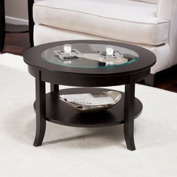 Eaton Coffee Table - The Eaton Coffee Table is the perfect choice as the centerpiece to your newly planned living room or den. Its round shape is complemented by a cantered lowered display shelf and a beveled clear-glass insert in the tabletop. The solid wood frame is sturdy and features bold lines emphasized by its deep espresso finish. This contemporary style coffee table makes a stunning accent to any room featuring wood or leather pieces. Some assembly is required.