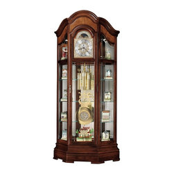 Howard Miller - Howard Miller Majestic Curio Grandfather Clock - 610939 - Shop for China from Hayneedle.com! The Majestic Curio Cabinet lives up to its regal name. This large curio cabinet doubles as a floor clock and is sure to stay in your family for generations. An arched pediment draws attention to the bookmatched rare olive ash burl overlays. The clock face is composed of a cast dial with intricate corner spandrels and the center disk boasts an astrological blue moon phase. This special cast design extends along the brass weights and pendulum. Crystal-cut grooved glass stands out on the lower door sides and escapement panels. The frame of this curio cabinet is finished in Windsor Cherry on select hardwoods and veneers and adjustable levelers are located under each corner to provide stability on uneven surfaces. Inside cable-driven triple-chime Kieninger movement keeps time faithfully and includes an automatic nighttime chime shut-off option. Six glass shelves are held securely in place by cushioned metal shelf clips. Behind the pendulum three shelves run across the width of the cabinet and can be adjusted to customize your display. A mirrored cabinet back reflects the beauty of your collection. The cabinet door is fitted with a lock for added security. Welcome an instant heirloom into your family when you order. Buy with confidence. We are an authorized Howard Miller dealer that provides you with a vast selection of quality products and excellent service you can trust. We understand choosing the perfect Curio Cabinet can be a difficult decision. Relax shop with confidence and buy from a company you can trust. Thank you for shopping with us. About Howard MillerBeginning in the 1920's Howard Miller clocks have impressed all who see them with superior quality and design. Howard Miller wall floor and mantel clocks are crafted to last for generations and to perfectly accent your home. The company's founder Howard C. Miller began manufacturing wall and mantel clocks in Michigan. Evolving to encompass cabinet making and other furniture design - all renowned for quality and style - the Howard Miller company proudly stands behind its reputation as the World's Largest Clock Manufacturer.