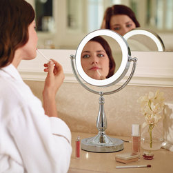 """Frontgate - Smart Touch Lighted Vanity Mirror - 7"""" mirror tilts to provide just the right angle, whether standing or sitting. Rotate 180° to flip from life-size to distortion-free 5x magnification. Tall pedestal design is a classic vanity accent. Warm, natural and face-level focused lighting is ideal for makeup application. Energy-efficient LED lighting. Bring elegant focus to your vanity and your beauty routine. Our exclusive Smart Touch Lighted Vanity Mirror automatically delivers your preferred level of soft, natural LED light. Simply tap the base to turn the light on, then press until you reach the desired brightness. This smart mirror will remember that setting the next time you turn it on.. Rotate 180 degrees to flip from life-size to distortion-free 5x magnification. . . . Simply tap to turn on/off . Easily adjust light level by touching the base. Memory function restores lighting to the previously used setting. In a non-corroding Satin Nickel, Polished Nickel or Polished Brass finish. 5 ft. cord."""