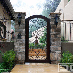 Dynamic Garage Door - Custom Entry Gates for a Mediterranean Style Home Located in Beverly Hills, CA - Beverly Hills, CA - Dynamic Garage Door custom designs, crafts and installs some of the most gorgeous Mediterranean Style Gates in California and ships all over the nation. Our expertise is in designing architectural gates that like in this project called for authentic Mediterranean Design. This iron and wood entry gate was cautiously designed to harmonize with the home's existing Mediterranean Architectural features. We softened the harshness of the iron fencing and scrolling by incorporating a wooden frame. This creates a warm invitation into the home's side courtyard complete with intercom strike release features which help the homeowner control access to the property by buzzing in guests or simply not allowing entrance to unwanted traffic. As the industry leader, Dynamic Garage Door, creates some of the most appealing gate designs that follow the existing home's architectural essence. This Beverly Hills, CA home required safety, aesthetics and quality garden gates that offered the best of all worlds. Fusing all these technologies and architectural styles is definitely something not every company offers out there. We understand those needs here at Dynamic Garage Door and that is why we cater our world-class creativity by means of our specialized design, craftsmanship and professional installation. So whether you're looking for an awesome gate for your house or for that of a client, perhaps a large estate, we can coordinate the design of all the exterior gates, garage doors, entry doors as well as window shutters if needed. We are the norm for truly authentic designs that will make your neighbors envious!