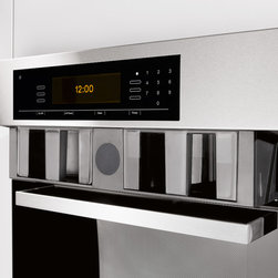 Miele Combi-Steam Oven - One of the design marvels of the Miele Combi-Steam Oven is its award winning lift-up control panel. Strategically hidden behind the panel are the water and condensate containers. A simple touch of a button automatically lifts the control panel providing easy access to replenish the water reservoir without having to open the oven door and interrupt the cooking process. Compared to the Miele Steam Oven, the new placement of the water reservoir also increases the oven's interior capacity by 40%, providing ample space for multiple dishes or large roasts to be cooked simultaneously.