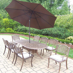 Oakland Living - 11-Pc Dining Set in Bronze - Includes table, eight dining chairs, 9 ft. tilt crank umbrella with stand and metal hardware. Handcast. Umbrella hole table top. Fade, chip and crack resistant. Traditional lattice pattern and scroll work. Hardened powder coat. Rust free. Warranty: One year limited. Made from cast aluminum. Antique bronze finish. Minimal assembly required. Table: 84 in. L x 42 in. W x 29 in. H (99 lbs.). Chair: 22.5 in. W x 22 in. D x 35 in. H (23 lbs.)The Oakland Mississippi Collection combines southern style and modern designs giving you a rich addition to any outdoor setting. This dining set is the prefect piece for any outdoor dinner setting. Just the right size for any backyard or patio.