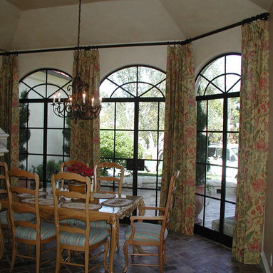 Custom Window Treatments - Stationary pinch pleated draperies installed on custom wrought iron hardware with rings meeting at the angled corner. The linen print fabric adds a touch of color to the room and frames the arched windows.