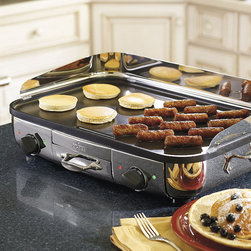 """Frontgate - All-Clad Electric Griddle - 2 separate heating elements provide fast, uniform heat transfer. Precision thermostat regulates the temperature from 250º to 450ºF.. Light indicator lets you know when the griddle reaches the desired temperature. Detachable stainless steel splatter guard helps keep countertops clean. Drippings are channeled into a removable dishwasher-safe tray. The generously proportioned All-Clad Electric Griddle is perfect for preparing pancakes, eggs, sausage, burgers, and more. This electric griddle features a dual zone, nonstick 20"""" x 13"""" cooking surface that allows you to simultaneously cook and warm 2 foods at different temperatures. . . . . . 1800 watts. 120V. This item is ineligible for discounts."""