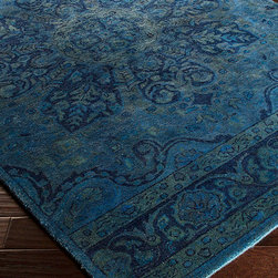 Mykonos Rug - Sky Blue, Teal, and Navy - The energizing composition of the Mykonos Rug � with a meditative oversized floral motif at the center and elegant scroll-framed borders at either short end � is second only to its powerful ocean color scheme for meditative, mood-setting effect.  Suffused with shades of sapphire, this elegant rug is hand-tufted from pure wool for an unusually plush feel.