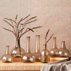 Champagne Vintage Bottles - Set of 7 - Hand-blown from recycled glass, the Champagne Vintage Bottles, sold in a set of seven slightly disparate shapes, boast tall, columnar necks that make floral arranging an easy pastime and add verticality to a room.  Arrange in a group, spread through a sun porch, or scatter in a china hutch or on a window shelf to take advantage of their romantic, aged effect.