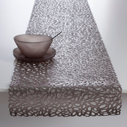 Chilewich - Chilewich Pebble Table Runner - Chilewich - Pebble, an original Chilewich molded design, was inspired by the organic shapes of stones on a beach. Reimagined and reinterpreted these shapes are translated into accessible styles for the tabletop. The openings in Pebble's mold naturally connect to one another creating a graphic that is a thoughtfully considered juxtaposition of the naturalness of actual pebbles. Available in Brass or Gunmetal. All Chilewich products, including table runner designs, are durable and easy to clean. Indoor/outdoor use.