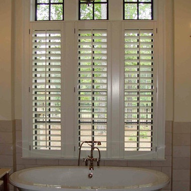 Elite Shutters in Bathroom Settings - This triple window over a claw foot tub features a three panel set of Elite Plantation Shutters in our 3 1/2'' louver size. This home is located in the River Club in Suwanee, Georgia.