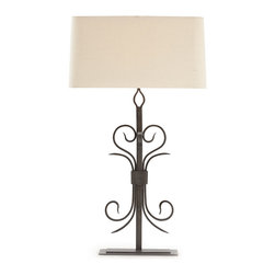Cranleigh Forged Natural Iron Lamp - Gently curved wisps of iron, reminiscent of the scrollwork gracing the garden gate of a European cottage, distinguish the Cranleigh Forged Natural Iron Lamp. Airy while at the same time substantial, the lamp boasts fluid iron curves mirroring one another and rising effortlessly along the length of the base. The low profile of the flat iron base allows the intricacies of the curvature to maintain a dramatic presence.