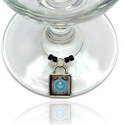 """Made on Terra - Alarm Clock Old Fashion Teal Gold Wine Glass Silver Charm - Your guests have arrived and the atmosphere is electric. A sip of wine here, a sip of a cocktail there and you find the conversation turning to the charming baubles you've placed on the glasses, something special you chose for each of your eclectic guests. They love them and appreciate your thoughtfulness. You love them for their uniqueness and that no one forgets which glass they were using.  Choose from Made on Terra's many designs for the best party ever. Ring is 1"""" diameter; measures 2"""" from top of ring to bottom of charm. Made of metal and plastic. Sold individually."""