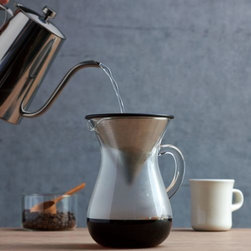 """Kinto - Slow Coffee Style Carafe Set by Kinto - Slow coffee is more than just a way of making your morning brew, it's part of a whole """"take things more slowly"""" lifestyle. The Kinto Slow Coffee Style Carafe Set makes the process even more appealing with its large rounded glass carafe, perfectly fitted stainless steel filter and a holder to keep the used filter upright until ready to clean (after you've had your first cup of coffee, of course). Kinto was originally founded more than 40 years ago to bring fine porcelain and ceramics to Japan. As of 2009, Kinto has shifted more toward the export of fine Japanese tablewares to the rest of the world. The designs of Kinto teapots, coffee pots and other kitchenware are continually fresh and unique, while maintaining the Japanese sensibility of conscientiousness and usefulness."""