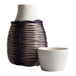 Pigeon Toe Ceramics - Woven Carafe, Solid Natural - Referencing a design dating back to the 15th century, our lidded porcelain carafe is covered in a handwoven basket in your choice of reed color(s) that provide a durable yet decorative cover. Topped with a lid that doubles as a cup, this vessel is perfect for the nightstand. Sold with 1 cup. Unglazed exterior / clear gloss interior. Shown in Black Indigo/Natural Stripe.