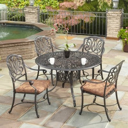 Home Styles Floral Blossom Patio Dining Set - Seats 4 - Take time out this summer to spend time with family and friends while enjoying a repast outdoors around the Home Styles Floral Blossom Patio Dining Set - Seats 4. Crafted from strong and durable cast aluminum, this patio table is powder-coated in a rich charcoal finish and features hand-applied antiqued highlighting to create a stunning look. The entire table is sealed with a clear coat for added protection so it'll continue to look beautiful for years to come. Add a splash of color and/or pattern to your table while keeping you and your guests protected from the sun by using an umbrella (not included) during those sunny days. You'll be able to move this table around your patio without having to worry about scuffing thanks to the nylon glides, which also help to provide stability on uneven surfaces. Four swivel chairs are perfect for relaxing in. Their swivel design allows you to follow or avoid the sun and makes it easy to get in and out. Ideal for dinners with family and friends, you'll also love having picnics with your children, and somewhere to sit and get work done while watching your kids play during the warm months. Additional Features Gorgeous, hand-applied antiqued highlighting Sealed with a clear coat for added protection Beautiful and intricate design on top 2-inch umbrella hole with black cap Nylon glides helps prevent damage on surfaces Glides provide stability on uneven surfaces Includes 4 comfortable swivel chairs Some assembly required About Home StylesHome Styles is a manufacturer and distributor of RTA (ready to assemble) furniture perfectly suited to today's lifestyles. Blending attractive design with modern functionality, their furniture collections span many styles from timeless traditional to cutting-edge contemporary. The great difference between Home Styles and many other RTA furniture manufacturers is that Home Styles pieces feature hardwood construction and quality hardware that stand up to years of use. When shopping for convenient, durable items for the home, look to Home Styles. You'll appreciate the value.