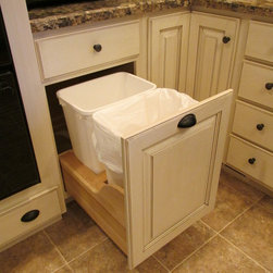 Kitchen Accessories - This double waste basket unit manufactured by WoodArt Fine Cabinetry features two large trash containers in a solid wood frame that is mounted on full extension soft-close slides.