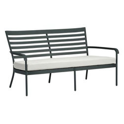 """Orleans Sofa with Sunbrella® White Sand Cushion - Elegant French Provencal curves nod to streamlined midcentury modern in this gracious and timeless outdoor collection. Park bench-style seating takes shape in durable yet lightweight aluminum tubing, powdercoated in a classic shade of evergreen. Slatted back angles for leisurely relaxing in a softly rounded frame, complete with retro-inspired """"covered"""" armrests. White sand chair cushion is covered in fade- and weather -resistant Sunbrella® acrylic with fabric tab fasteners to hold it in place. Orleans dining collection also available."""