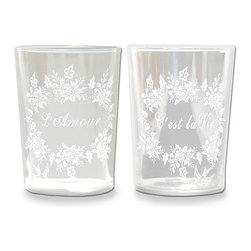 """L'amour C'est la Vie"" Glass - Exuberant wreaths of foliage surround exquisite scripts of convivial French phrases � ""L 'amour"" and ""C'est la Vie"" � on a frosted glass tumbler that gives a festive feel to any occasion. Not seasonal but certainly topical, this glassware piece for the formal dining table or for the bedside of a guest room is simple in outline but displays a lacy design with dramatic, universal grandeur."