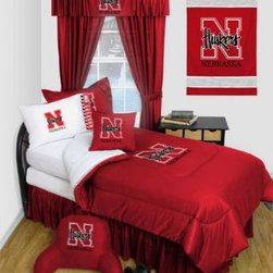 Sports Coverage - Nebraska Cornhuskers NCAA Locker Room Complete Bedroom Package - Queen - Save big and show your team spirit with Nebraska Cornhuskers Complete Bedroom Package which includes a Comforter, Sheet set, Shams, Pillows, Bedskirt and Valance! Buy this Complete Bedroom Package and save off our already discounted prices - the best we could find; when you buy the complete bedroom package instead of each piece separately, you save and save big.   Microfiber Sheet Hem sheet sets have an ultrafine peach weave that is softer and more comfortable than cotton.  Its brushed silk-like embrace provides good insulation and warmth, yet is breathable.  The 100% polyester microfiber is wrinkle-resistant, washes beautifully, and dries quickly with never any shrinkage. The pillowcase has a white on white print beneath the officially licensed team name and logo printed in vibrant team colors, complimenting the NEW printed hems. The Teams are scoring high points with team-color logos printed on both sides of the entire width of the extra deep 4 1/2 hem of the flat sheet.    2 flanged edge that decorates all four sides of each Pillow sham. Made of 100% polyester jersey mesh, just like the players wear.  Bedskirt available in team color with no team logo printed on them.   Includes:  -  Comforter - Twin 66 x 86, Full/Queen 86 x 86,    -  Flat Sheet - Twin 66 x 96, Full 81 x 96, Queen 90 x 102.,    - Fitted Sheet - Twin 39 x 75, Full 54 x 75, Queen 60 X 80,    -  Pillow case Standard - 21 x 30,    - Pillow Sham - 25 x 31,    -  Bedskirt - Twin 76 x 39, Full 76 x 54, Queen 80 x 60 ,    - 18 Toss Pillow ,    - Window Drapes: 82x 63 ,    -  Window Valance : 88 x 14 ,