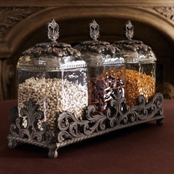 "GG Collection - GG Collection Three Glass Canisters - Three textured glass canisters topped by elaborately detailed metal lids are held within a metal stand. From the GG Collection. Each canister, 6""Sq. x 13""T. Stand, 19.5""L x 6.75""W."