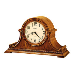 "Howard Miller - Howard Miller - Hillsborough Mantel Clock - In the spirit of 18th century classicism, this great mantelpiece shines in any room. Beautifully lined with wood carvings and intricately designed metal hands, this clock perfectly perches on any desk or shelf. With wonderful dips and swirls, this piece is designed with a sense of shape. * Highlighted with bookmatched oak molding that frames the dial and offers scrolls on the sides. . The ivory dial offers Arabic numerals. . A beaded molding accents the front and sides. . Finished in Oak Yorkshire on select hardwoods and veneers. . Quartz, dual chime movement plays Westminster or Ave Maria chimes, and features volume control and automatic nighttime chime shut-off option. H. 11-1/4"" (29 cm). Color shade may vary due to the natural tone of the wood. W. 19"" (48 cm). D. 6-3/4"" (17 cm)"