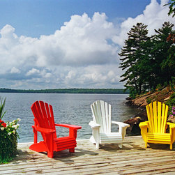 Murals Your Way - Sunny Days Wall Art - Three Adirondack chairs, brightly painted red, white and yellow and flanked by large pots of blooming flowers, sit at the edge of a large lake in