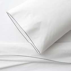 Belo Grey Twin Sheet Set - Clean, basic white bedding upgrades in soft, smooth cotton percale, beautifully contrasted with a graceful grey overlocking stitch on the flat sheet and pillowcase. Generous fitted sheet pockets accommodate thicker mattresses. Sheet set includes one flat sheet, one fitted sheet and one standard pillowcase. Bed pillows also available.
