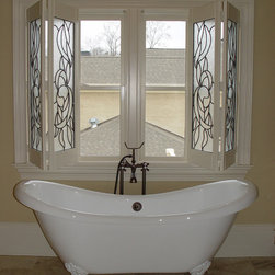 Elite Shutters in Bathroom Settings - This is a custom bi-fold shutter that Elite built for a bathroom window with a stained glass panel insert shown in an open position.